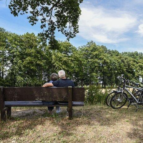 stel-man-vrouw-bos-bank-bankje-bomen-gras-fietsen.jpg